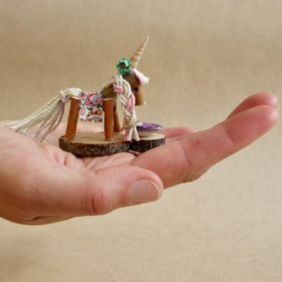 Naturmake model of a tiny unicorn in the palm of a hand